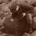A picture of a man gold panning